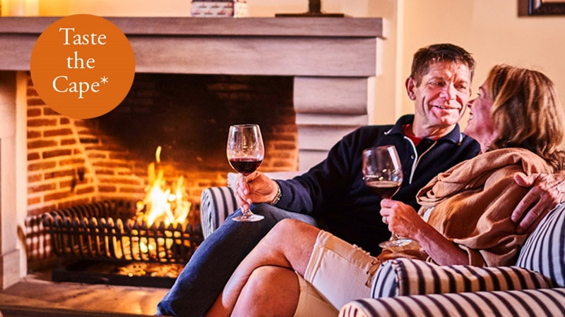 2 people sitting at the fireplace with a glass of wine