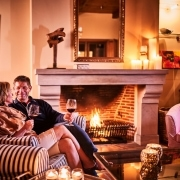 2 people sitting at the fireplace
